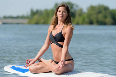portrait of a woman meditating on paddleboard