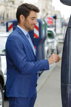 man paying for his parking ticket on the machine Standard-Bild