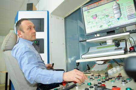 man typing at factory computer