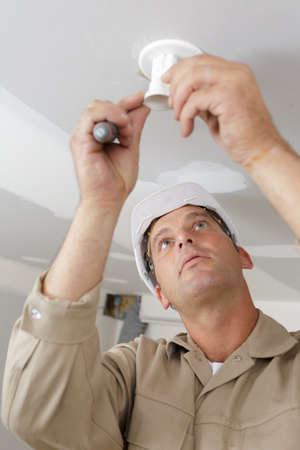 male contractor installing light fitting