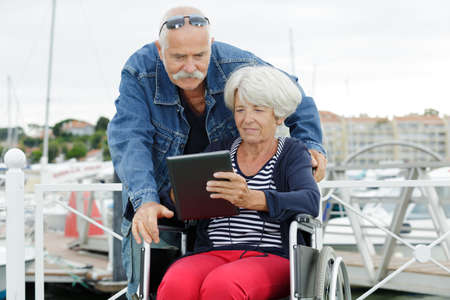 senior couple looking at tablet woman in wheelchair