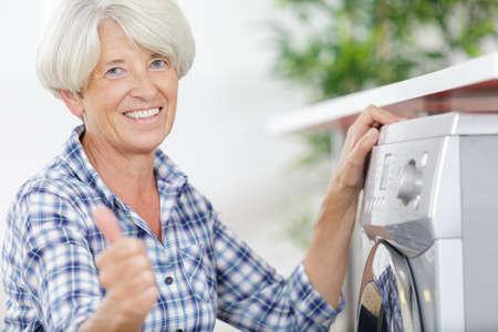 happy senior doing home laundry