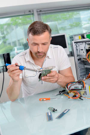 man is soldering a video card Imagens