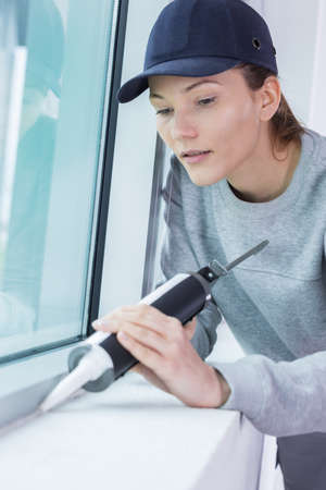 female construction worker installing window in house Stock Photo