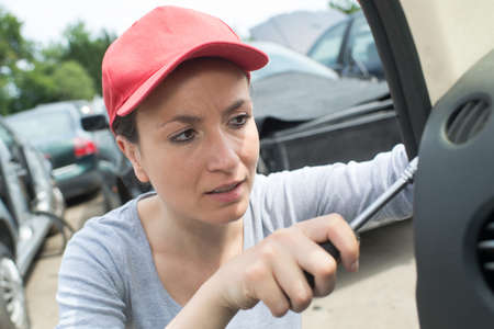 professional auto woman mechanic and man repair auto outdoors