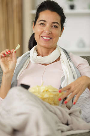 woman at home watching tv and eating chips Stock Photo