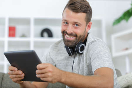 man in phones with tablet pc listening to music