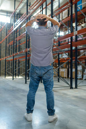 man looking in despair at empty racking in warehouse