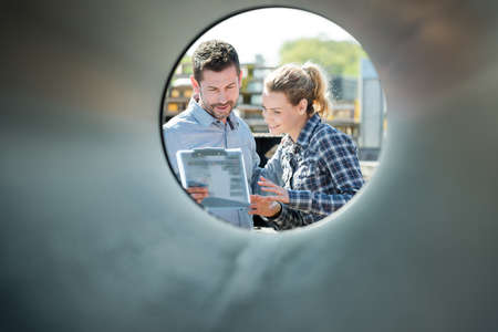 man and woman being looked through a pipe