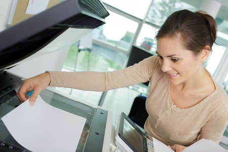 woman placing paper on office photocopy