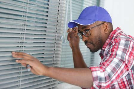 a man adjusting window blind