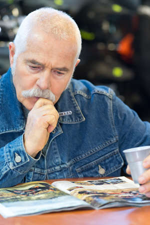 senior man looking at motorcycle magazine 版權商用圖片