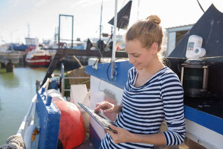 woman leaning against a fishing vessel Banque d'images