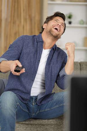 man watching television making victory gesture