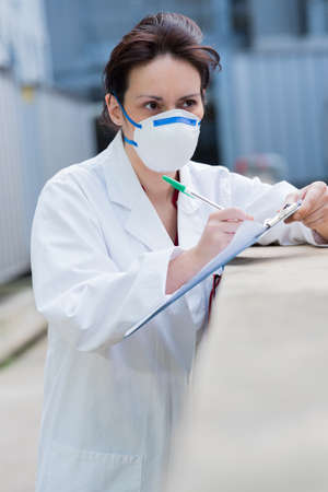 woman with a mask checking clipboard