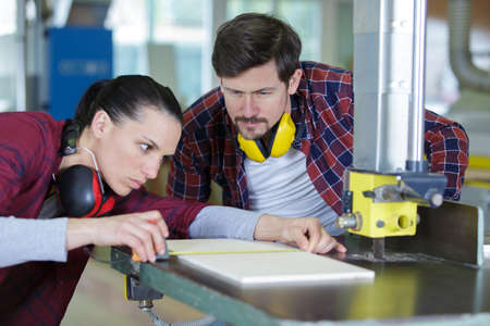 female carpenter working with wood under control of coworker