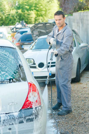 male worker rinsing the car Imagens