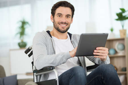 wheelchair bound man using a tablet pc