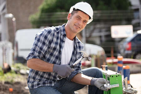 mature construction worker laying foundations