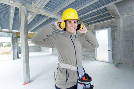 female builder putting on her earmuffs