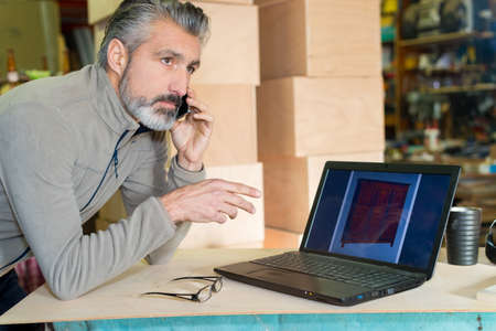 cabinet maker talking on phone looking at design from laptop