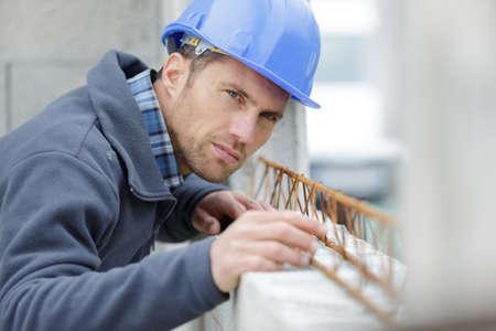 a man measuring window outdoors