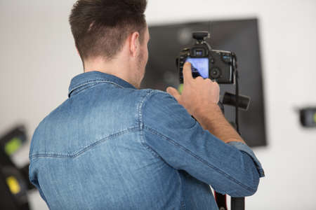 professional photographer shooting in his studio with a dslr camera