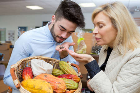 grocer and customer smelling exotic fruits