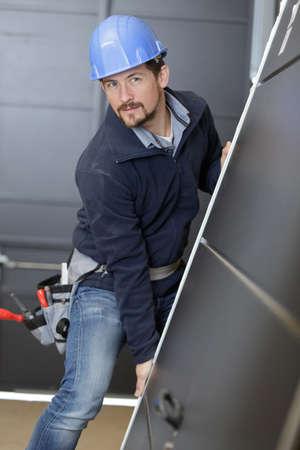 middle-aged worker holding a door Foto de archivo