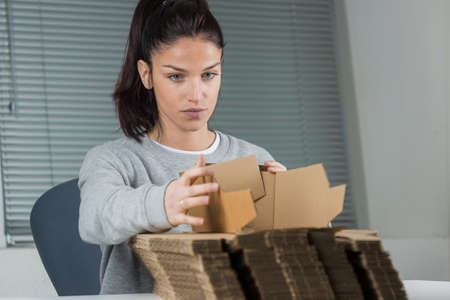 young female worker assembling cardboard box
