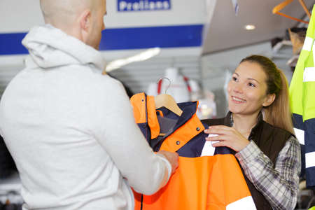 man and woman choosing a jacket in a clothes store