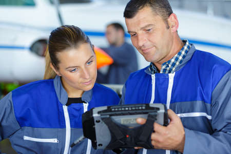 young female aircraft assembler listening to trainer