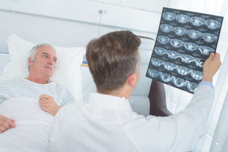 doctors checking patients xray in hospital room