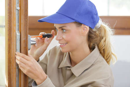 female contractor using screwdriver to fit new handle Reklamní fotografie