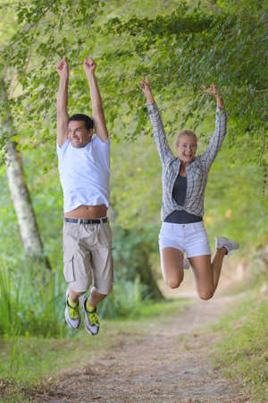 a couple jumping after completing their outdoor hike
