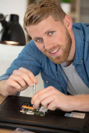 happy man using screwdriver and repairing a broken laptop