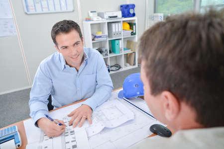 Two men at desk discussing blueprints Banco de Imagens