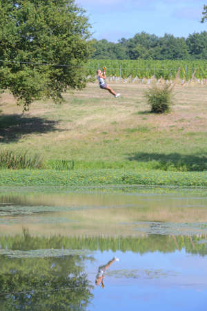 Person on zip line, reflected in lake