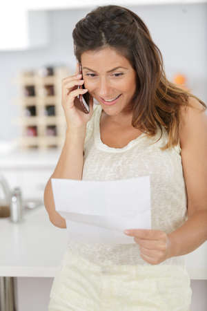 woman on the telephone imparting news received by letter