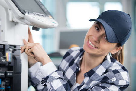 happy woman fixing a printer