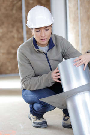 woman builder holding ventilation pipes