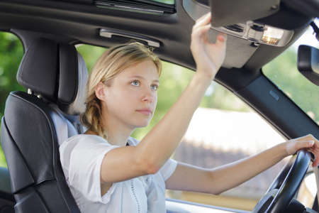 young woman driver adjusting her rearview mirror in the car Zdjęcie Seryjne