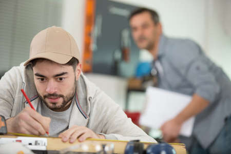 man worker with a pencil makes notes in workshop