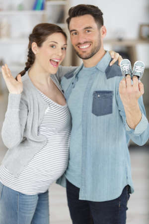 pregnant couple holding baby shoes in living room