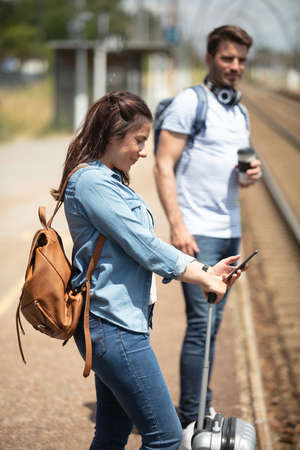 couple waiting on the platform woman using a smartphone
