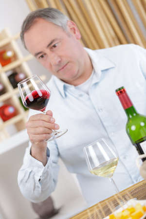 elderly man looking at a red wine in the glass