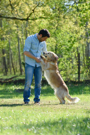 a man playing with dog