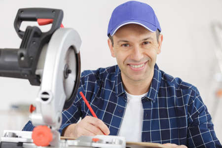 portrait of mature man working with circular saw