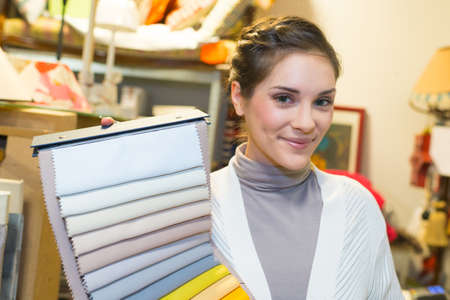 beautiful female designer with textile swatches in office
