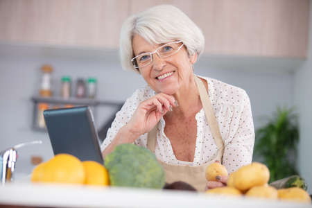 woman following recipe on website to make healthy smoothie